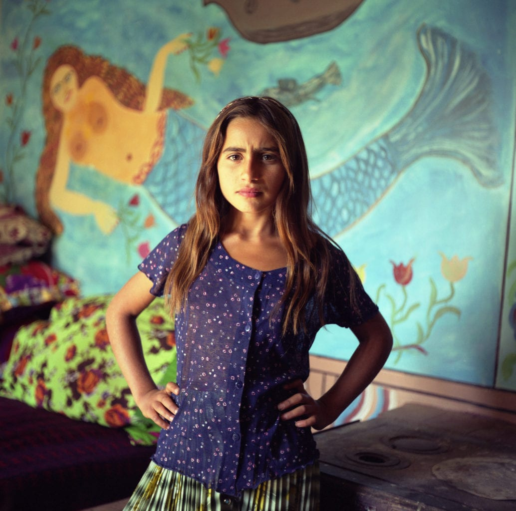 Mia, a young Roma girl stands in front of a mermaid painted on the wall of a Roma home, in the old part of the Roma camp of Sintesti, Romania, in Setember 2004.
